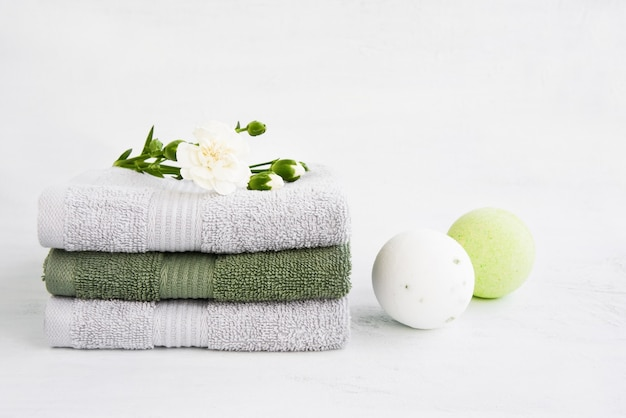 Spa concept. two bath bombs and bath towels decorated with carnation flower on light background. copy space for text