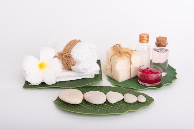 Spa concept, white stone, red candle, rose liquid soap, towel, flowers  on green leaves