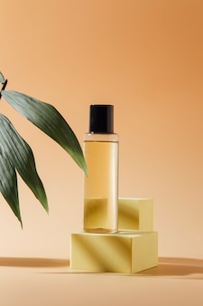 Концепция спа с бутылками эфирного масла и цветов на бежевом фоне