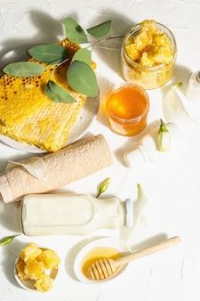 蜂蜜とミルクを使ったスパのコンセプト。天然化粧品、有機成分。ハードライト、ダークシャドウ。白いパテの背景、上面図