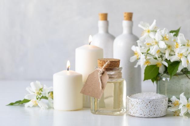 Концепция спа с маслом жасмина, с солью для ванн и цветами на белом фоне. спа и оздоровительный натюрморт. скопируйте пространство.