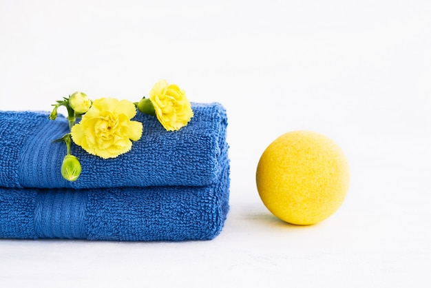 Spa concept. yellow bath bomb and two blue towels decorated with carnation flower on light
