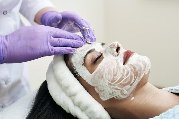 スパのコンセプト。ビューティーサロンで栄養フェイシャルマスクを持つ若い女性、クローズアップ。美容師は、クライアントの顔に保湿マスクを適用します。