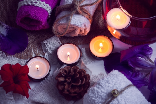 Spa consist from towels, candles, flowers, cone and aromatherapy water in a glass bowl
