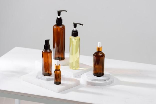 灰色のコンクリートのテーブルの上の茶色のガラス瓶のスパ化粧品。テキスト用のスペースをコピーします。美容ブロガー、サロンセラピー、ブランディングモックアップ、ミニマリズムのコンセプト
