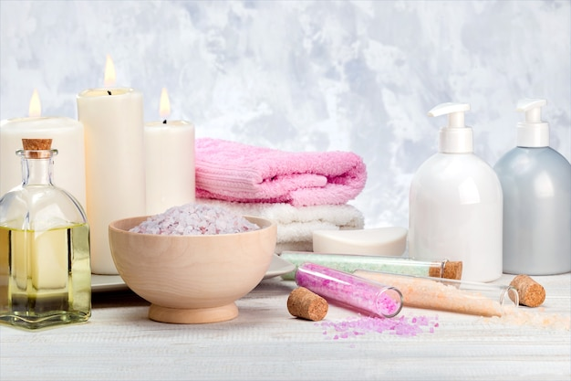스파 화장품 제품, 로션, 크림, 목욕 소금, 에센셜 오일, 비누, 나무 선반에 수건.