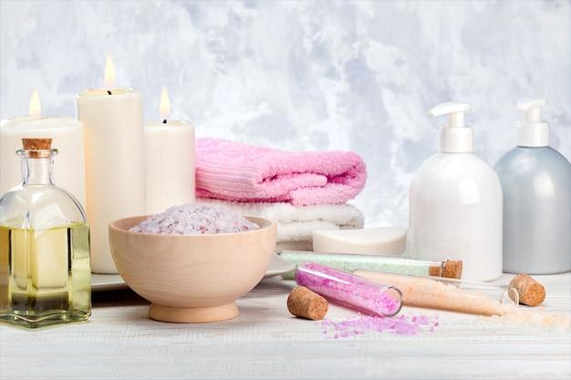 Spa cosmetics products, lotion, cream, bath salt, essential oil, soap, towels on wooden shelf.