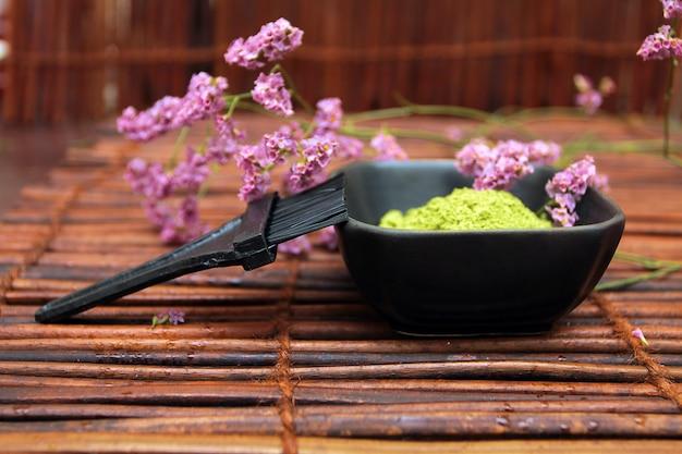 スパ化粧品シリーズ。化粧品の泥と花とマットを背景にブラシ
