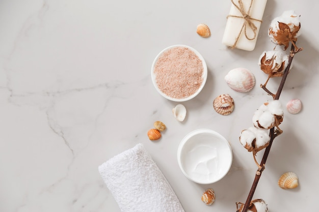 Spa cosmetics set on white marble from above