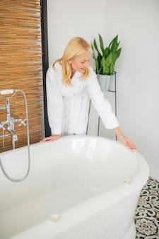 自宅でのスパの日。浴室に立っている白いバスローブのかわいいブロンドの女性