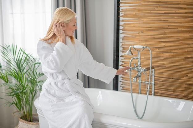 スパの日。お風呂の準備をしている白いバスローブを着た金髪のきれいな女性