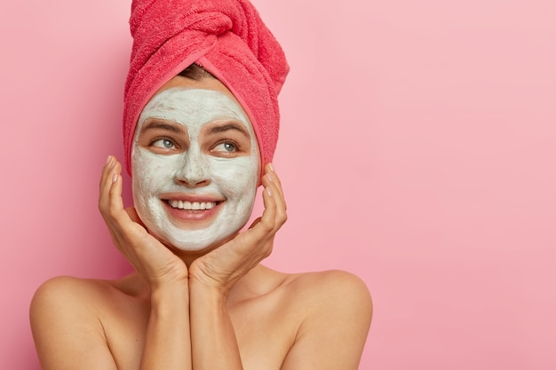 Spa day concept. beautiful happy woman smiles positively, shows teeth, touches gently face, applies beauty mask for rejuvenation and cleaning pores, has naked body, looks aside against pink wall