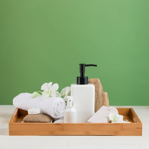 Spa украшение. состав спа с косметической бутылкой над зеленым цветом.