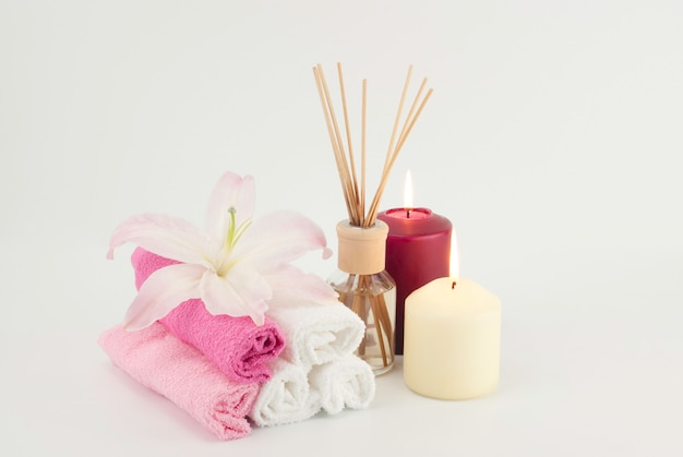 Spa decoration with candles, towels and aromatherapy oil bottle