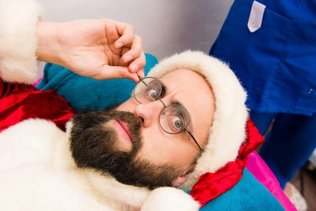 スパフェイシャルマスクアプリケーション。美容スパでサンタクロースの服のクリスマス男。 Premium写真