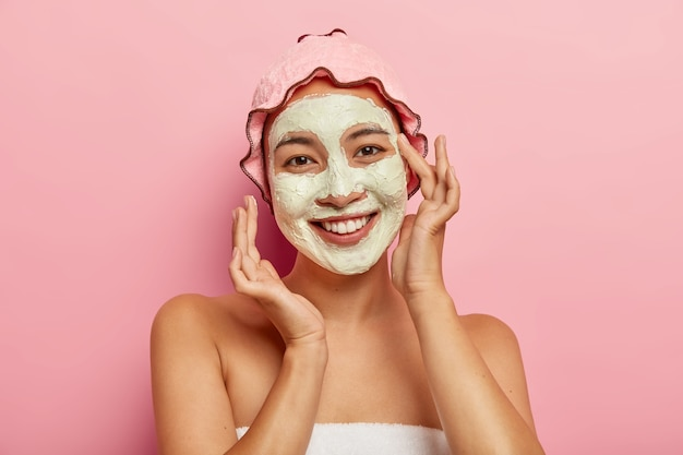 Spa facial mask application. happy delighted young woman with asian appearance, improves skin condition with clay mud, applies cosmetic product on face, takes care of her complexion and body