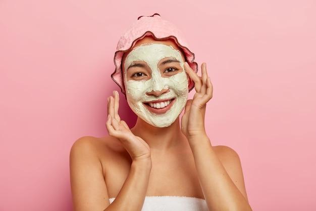 스파 페이셜 마스크 적용. 아시아의 모습으로 행복하게 기뻐하는 젊은 여성, 진흙 진흙으로 피부 상태를 개선하고, 얼굴에 화장품을 바르고, 안색과 몸을 관리합니다.