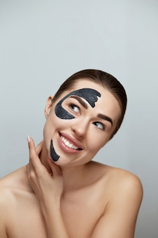 Spa facial mask. beautiful young woman with black mask of clay on face .skin care .girl model with  moisturizer cosmetic mask. facial  treatment