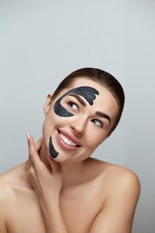 Спа-маска для лица. красивая молодая женщина с черной маской глины на стороне. забота кожи. модель девушки с маской увлажнителя косметической. уход за лицом