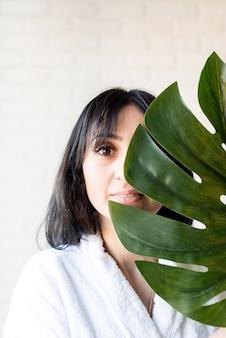 스파 페이셜 마스크. 스파와 아름다움. 그녀의 얼굴 앞에 녹색 몬스 테라 잎을 들고 목욕 가운을 입고 행복 한 아름 다운 갈색 머리 중동 여자