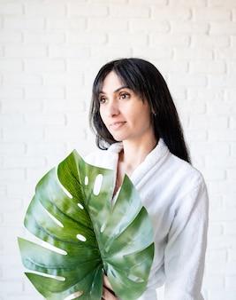 스파 페이셜 마스크. 스파와 아름다움. 녹색 monstera 잎을 들고 목욕 가운을 입고 행복 한 아름 다운 갈색 머리 중동 여자