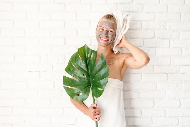 스파 페이셜 마스크. 스파와 아름다움. 녹색 monstera 잎을 들고 그녀의 얼굴에 클레이 페이셜 마스크와 목욕 수건을 입고 행복 한 웃는 여자