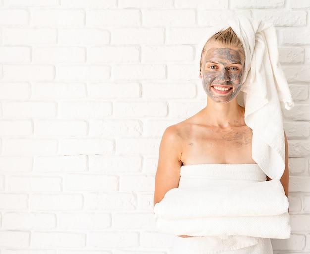 스파 페이셜 마스크. 스파와 아름다움. 그녀의 얼굴에 클레이 페이셜 마스크와 흰색 목욕 수건을 들고 젊은 웃는 여자