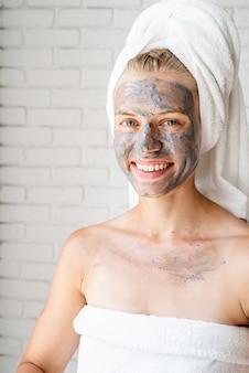 스파 페이셜 마스크. 스파와 아름다움. 그녀의 얼굴에 클레이 페이셜 마스크와 흰색 목욕 수건을 입고 젊은 웃는 여자