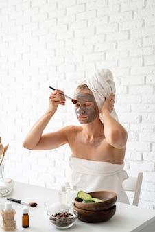 스파 페이셜 마스크. 스파와 아름다움. 화장품 브러시로 그녀의 얼굴에 스파 페이셜 마스크를 적용하는 흰색 수건을 입고 젊은 여자