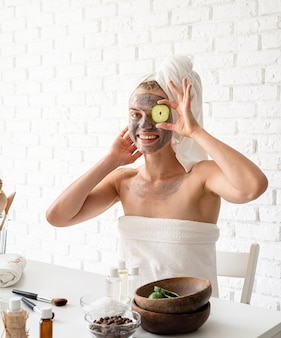 Spa facial mask. spa and beauty. young woman wearing white towels applying spa facial mask on her face with a cosmetic brush
