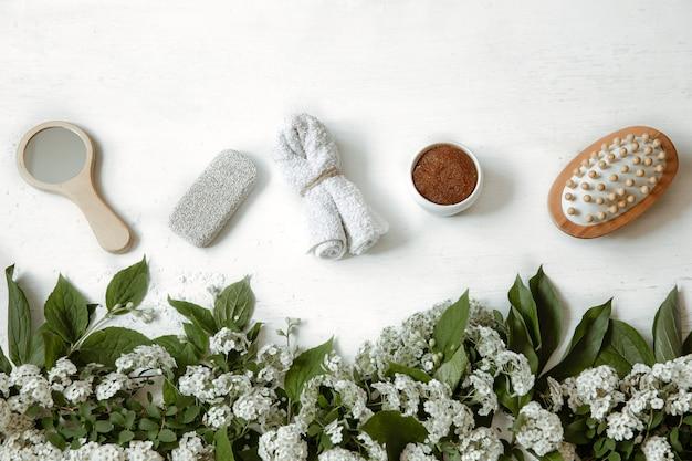 Composizione piatta spa con accessori da bagno, prodotti per la salute e la bellezza con fiori freschi.