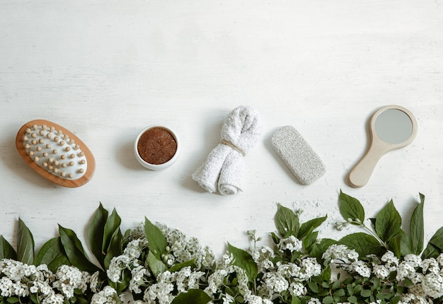 Spa flat lay composition with bath accessories, health and beauty products with fresh flowers