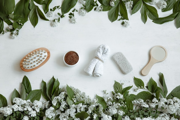 Spa flat lay composition with bath accessories, health and beauty products with fresh flowers.