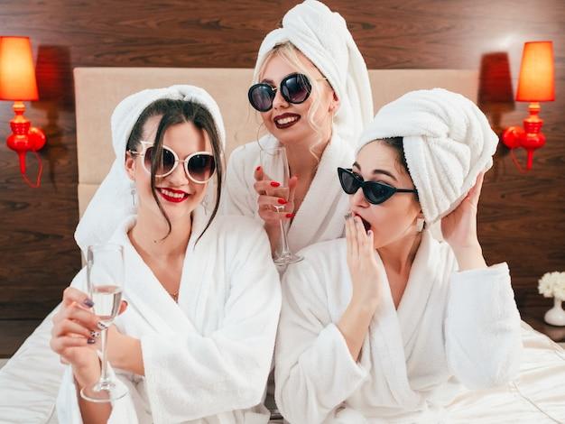 スパの楽しさとリラクゼーション。サングラス、バスローブ、ターバンを着た女性。手にシャンパン。パーティーオーバー。あくびをする女性。 Premium写真