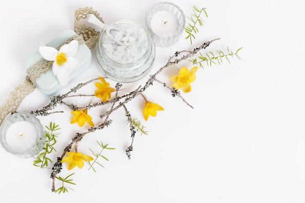 Spa gentle spring background with spring yellow flowers and twigs, candles, spa salt on white