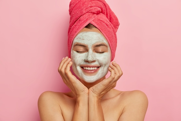 Spa girl applies clay mask on face, keeps eyes closed, touches cheeks, gets pleasure from beauty procedure, refreshes skin, smiles positively isolated on pink wall. relaxation, healthy lifestyle