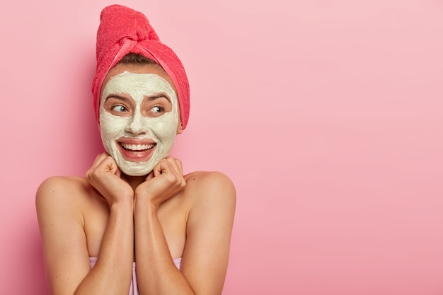 Spa girl smears muddly texture across face, has glad look, keeps hands under chin, looks away with smile, hydrates and calms skin, wears red towel on head, excess oil production, stands naked indoor