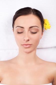 Девушка спа. вид сверху привлекательной молодой женщины с цветком в голове, лежа и с закрытыми глазами