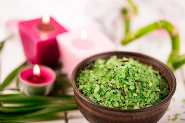 Spa. green herbal spirulina salt in ceramic bowl, spa towels, pink scented candle and bamboo.