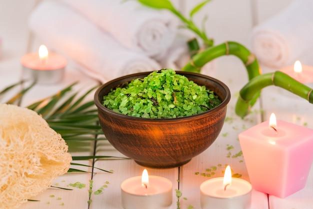 スパ。セラミックボウル、スパタオル、ピンクの香りのキャンドル、竹のグリーンハーブスピルリナ塩。