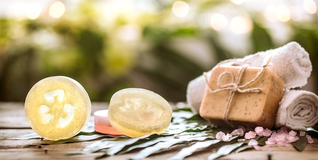 Spa handmade soap and a towel, the composition of the tropical leaves wooden background