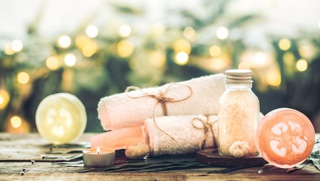 白いタオルと海の塩、キャンドル、木製のテーブルと熱帯の葉の組成を持つスパ手作り石鹸