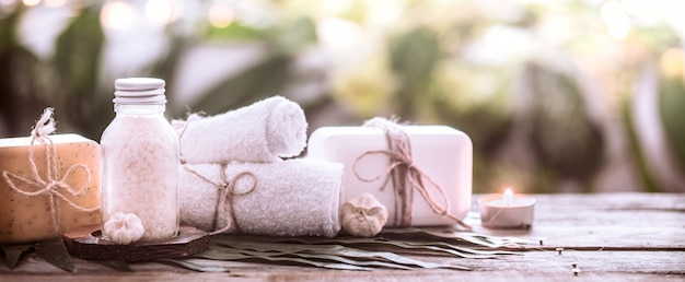 Spa handmade soap with white towels and sea salt, the composition of the tropical leaves with a candle, wooden background