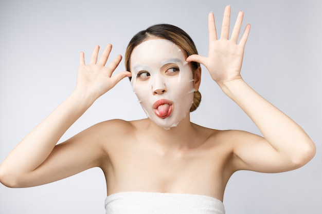 Spa, healthcare. asian girl with a cosmetic mask isolate on white.