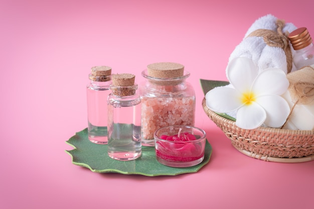 Spa  himalayan salt, red candle, milk  and rose liquid soap, white towel, flowers  set on green leaves over pink