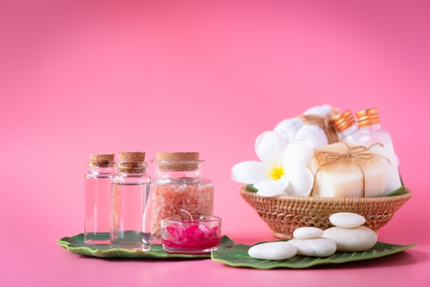 Spa  himalayan salt, red candle, milk and rose liquid soap, white towel, flowers , zen stone set on green leaves over pink