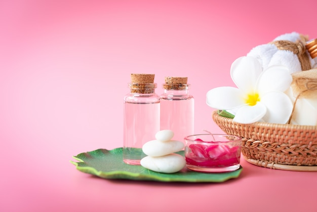 Spa  himalayan salt, red candle, milk  and rose liquid soap, white towel, flowers, zen stone set on green leaves over pink