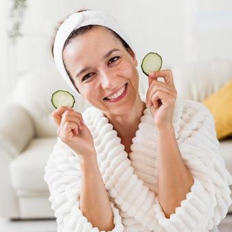Spa a casa donna sorridente che tiene le fette di cetriolo