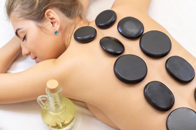 Спа массаж горячими камнями. привлекательная красивая девушка, лежа на массажной кровати в спа-салоне