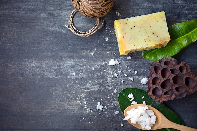 Spa ingredients, white salt, yellow homemade soap, tropical green leaves on dark wood
